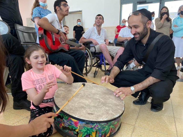Philharmonic drummer and young girl at ADI מתוףף מהתזמורת עם ילדה בעדי